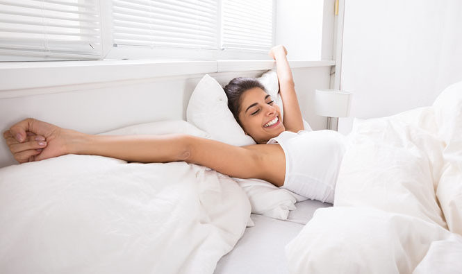 Mujer despertándose por la mañana en su habitación.