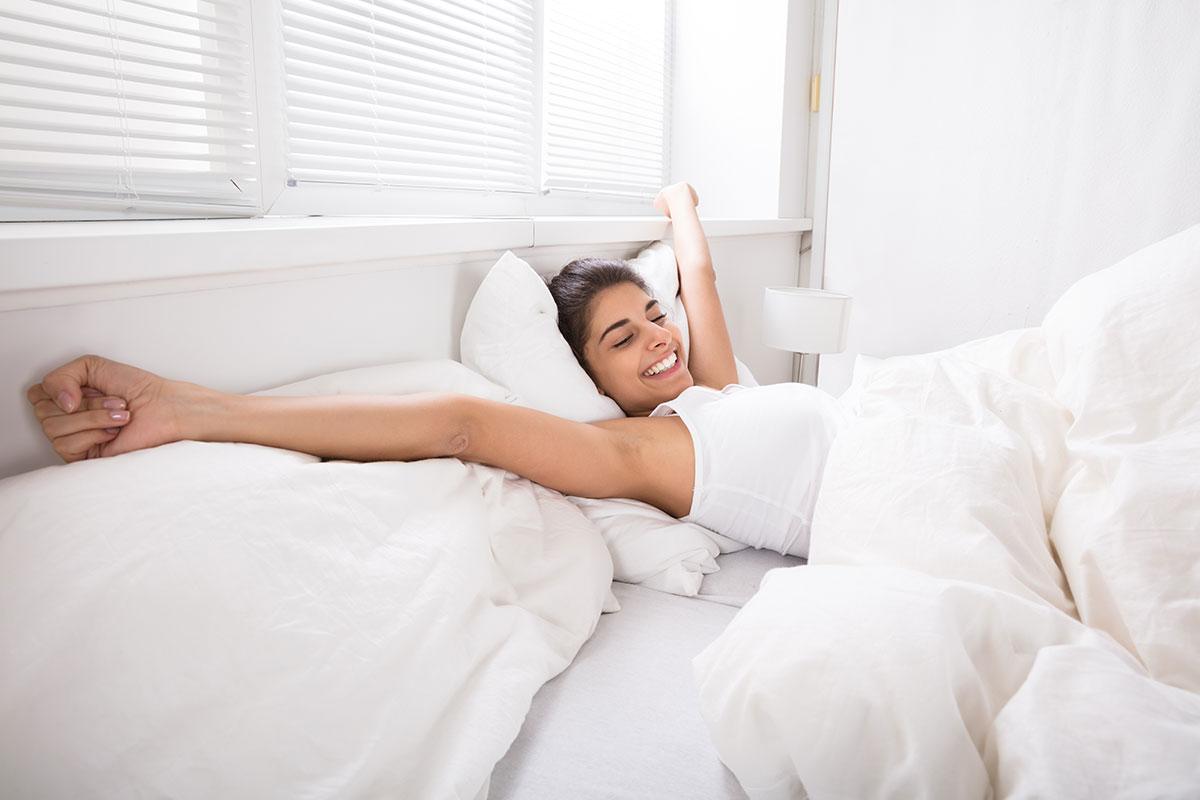 Mujer despertándose por la mañana en su habitación