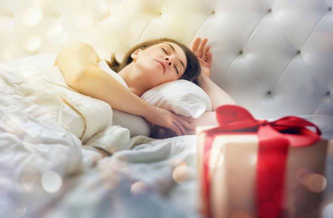 Mujer durmiendo al lado de un regalo de Navidad
