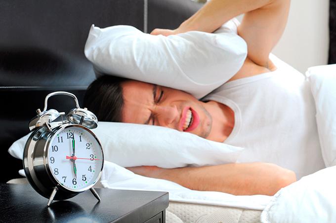Chico despertándose enfadado al sonar el despertador