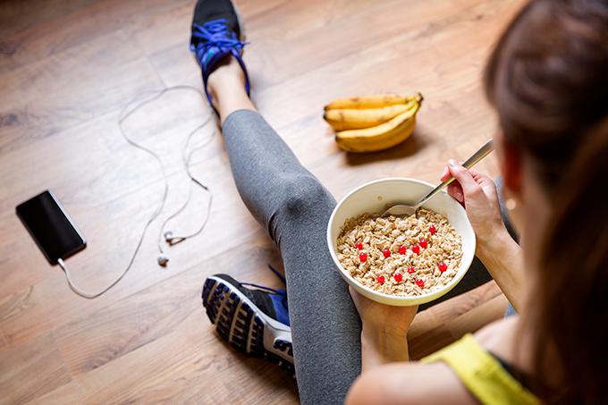 Chica vestida con ropa de deporte comiendo un bol de cereales