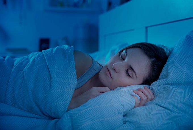 Chica echando la siesta en la cama con la habitación a oscuras