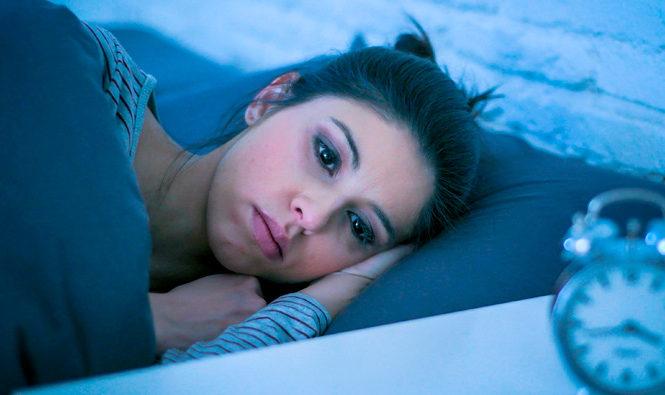 Chica en la cama con los ojos abiertos sin poder dormir