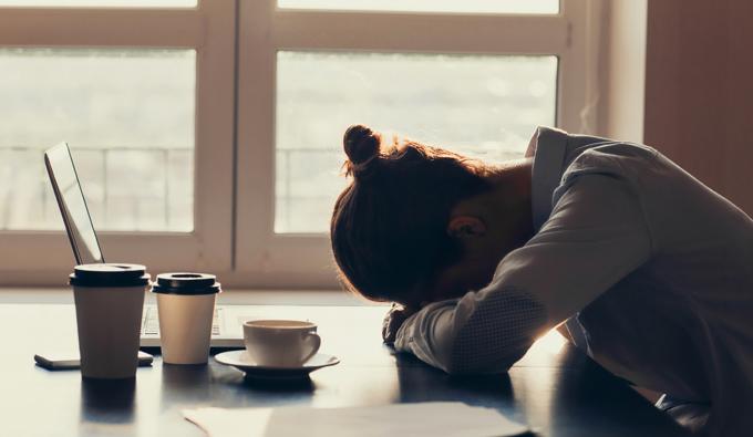 Chica en el trabajo con la cabeza sobre la mesa y el café al lado suyo