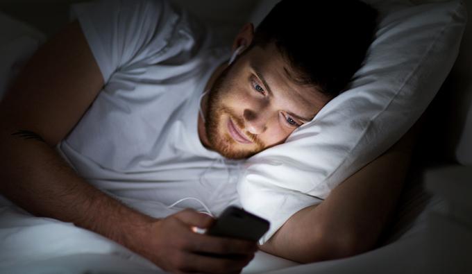 Chico en la cama usando el móvil