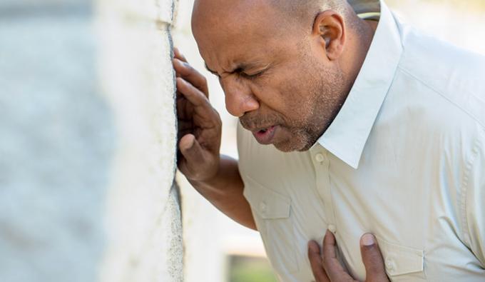 Hombre con la mano sobre el pecho con gesto de dolor