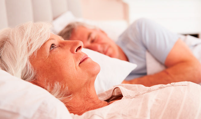 Mujer mayor tumbada en la cama con los ojos abiertos