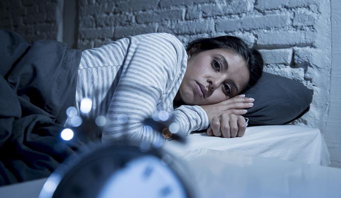 Chica con insomnio tumbada en la cama sin poder dormir