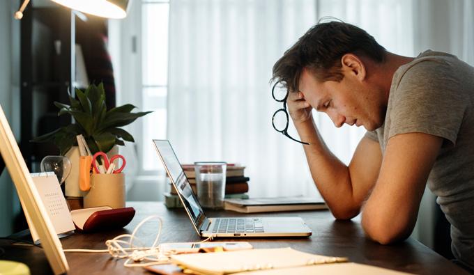 Hombre estresado mientras trabaja con el portatil