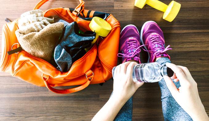 Bolsa de deporte y manos de chica bebiendo agua