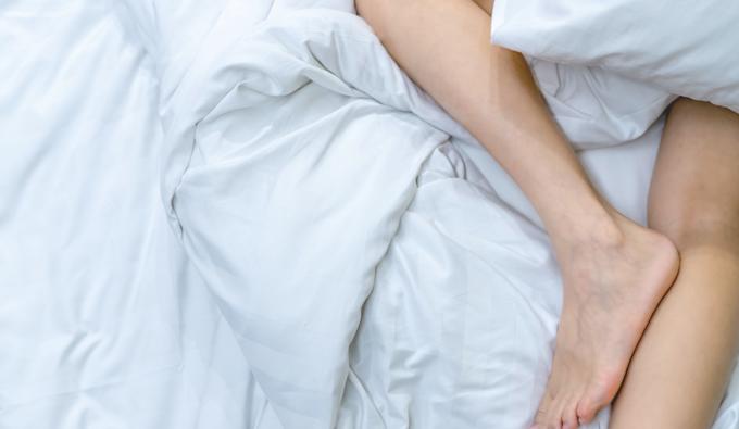 Piernas en una cama entre las sabanas
