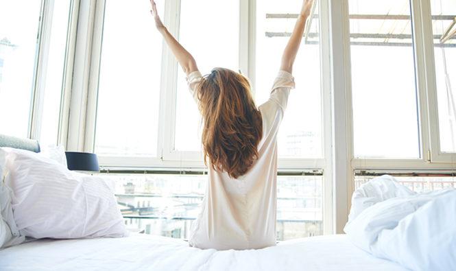 Mujer estirandose tras haber descansado bien en la cama