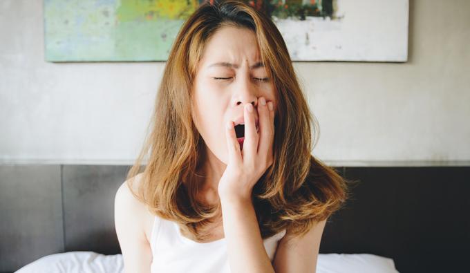 Chica bostezando en la cama