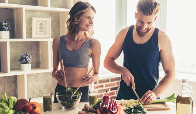 pareja preparando comida saludable