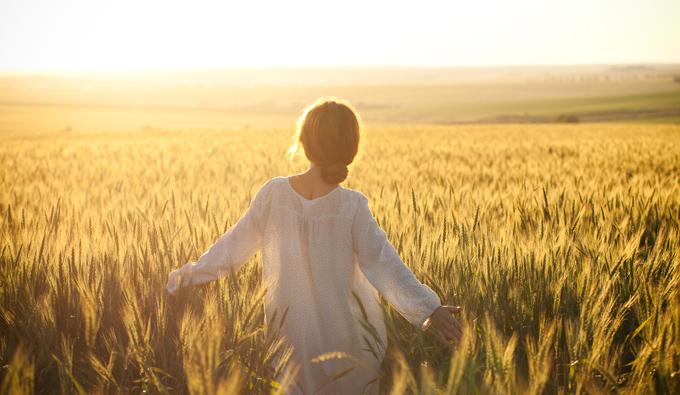 Chica caminando por el campo en primavera