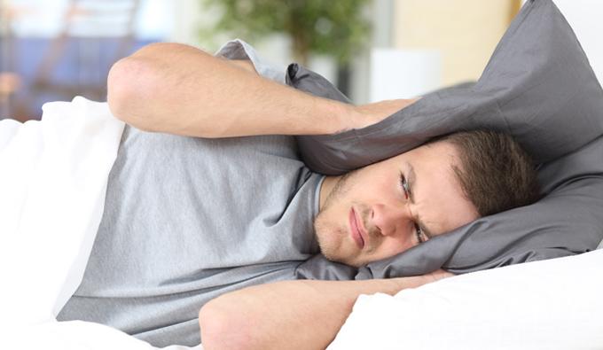 Chico en la cama sin poder dormir por el ruido