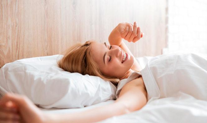 Chica despertando después de un buen descanso sobre colchón