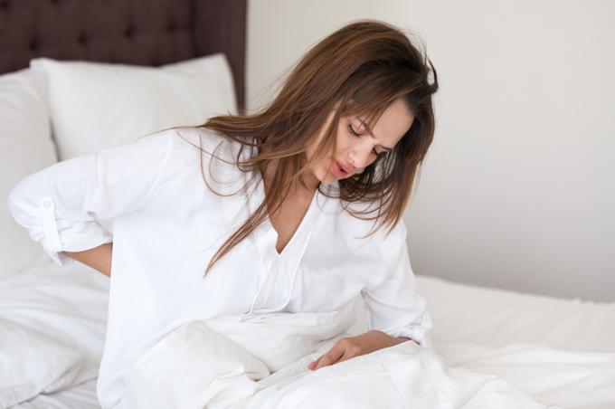 Chica en la cama con dolores musculares