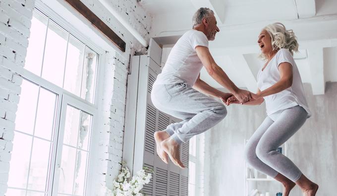 Oferta SB Descanso, 0% intereses 100% descanso, dos personas mayores saltando en la cama